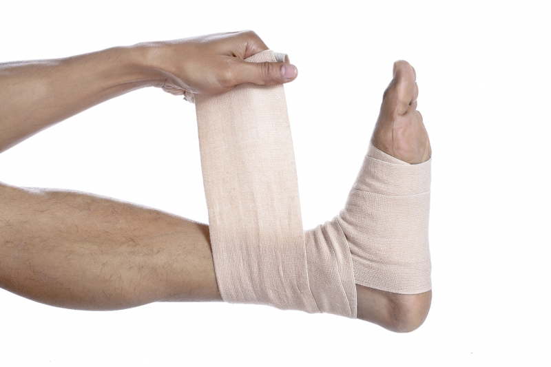 4003375-guy-placing-a-tensor-bandage-on-his-feet